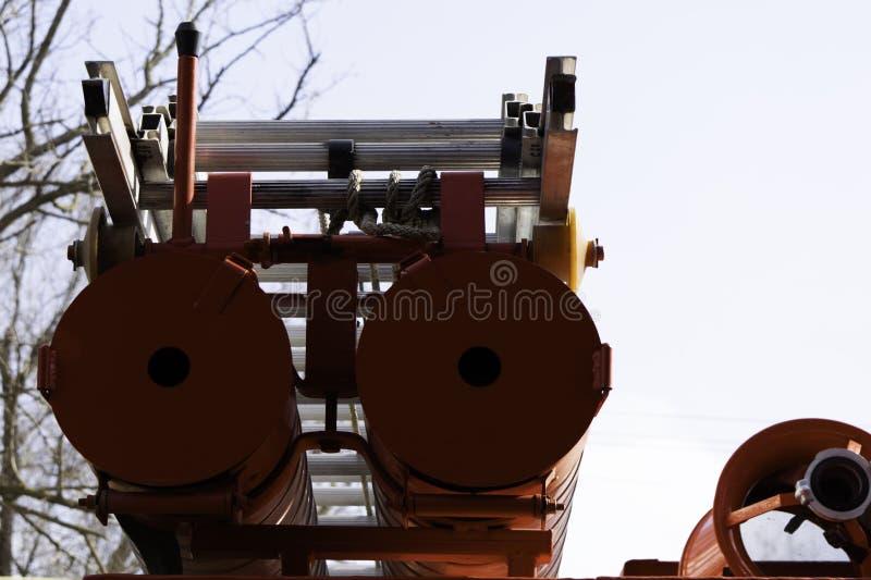 Brandlastbil, bakre sikt av kanistrar för transportering av sugslangar med brandflykter som fästas till dem royaltyfri fotografi
