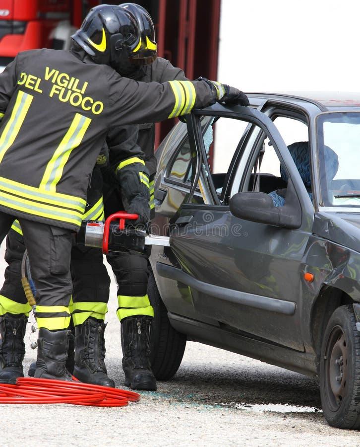 Brandmän öppnar dörren av bilen med kraftig sax royaltyfria foton