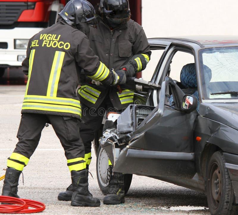 Brandmän öppnar dörren av bilen med pneumatisk sax royaltyfri bild