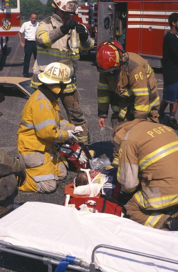 Brandmän arbetar på sårad person royaltyfria bilder
