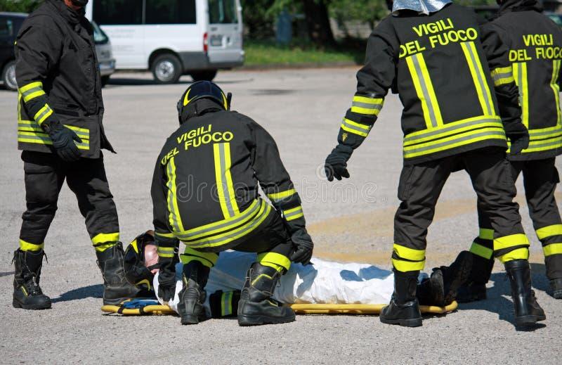 Brandmän bär en bår med allvarliga skador efter aet royaltyfri bild