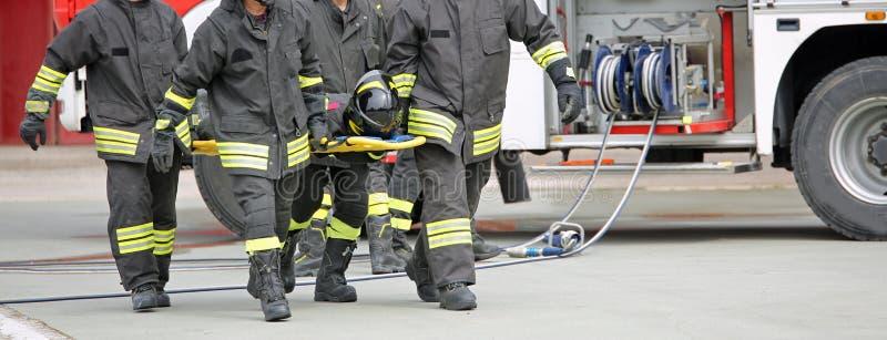 Brandmän bär en sårad person royaltyfria foton