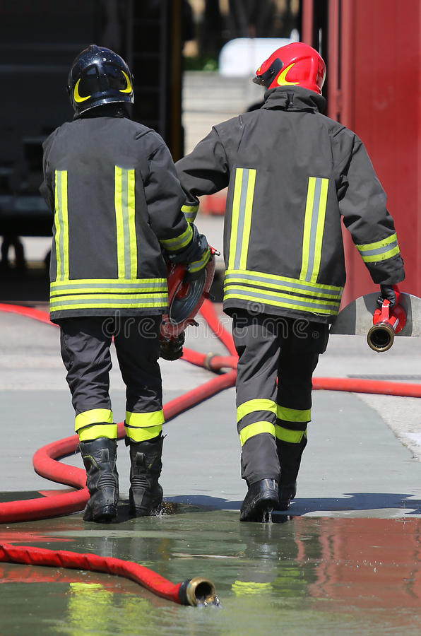 Brandmän bär vattenpost- och slangrören efter satt av royaltyfri bild