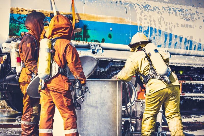 Brandmän i brandmanlikformig kontrollerar deras utrustningafte arkivbild