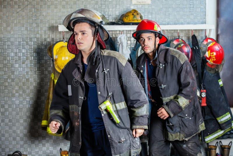 Brandmän i likformig som går på brandstationen royaltyfria foton