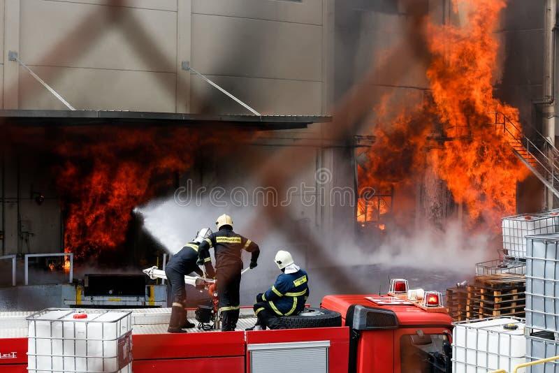 Brandmän kämpar för att släcka branden som bröt ut på a arkivbild