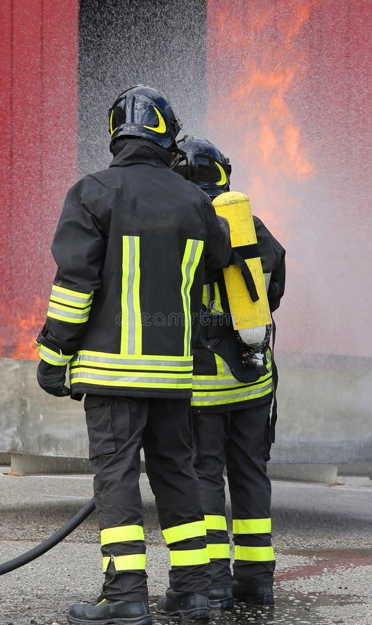 Brandmän med syreflaskor av branden under en utbildning arkivbilder