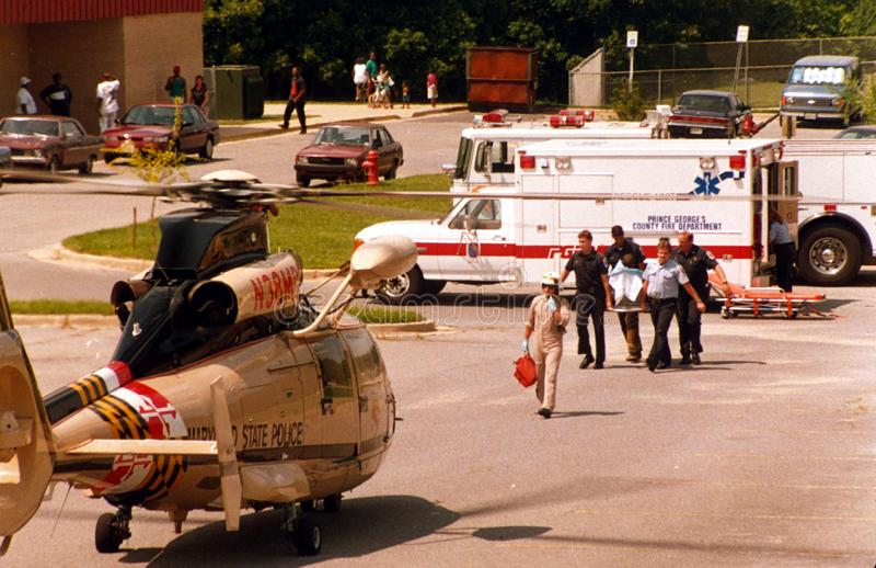 Brandmän och läkare bär en sårad person till en väntande helikopter arkivfoton