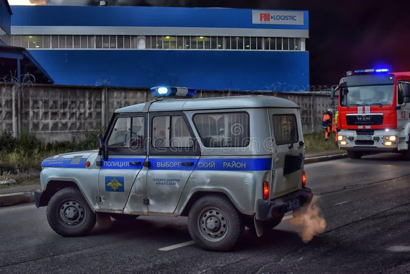 Brandmän och polisbilar på brand - släcka i den industriella zonen royaltyfria bilder