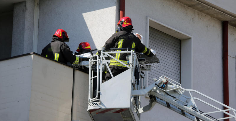 Brandmän på buren för brandlastbilen sparar den sårade personen royaltyfria foton