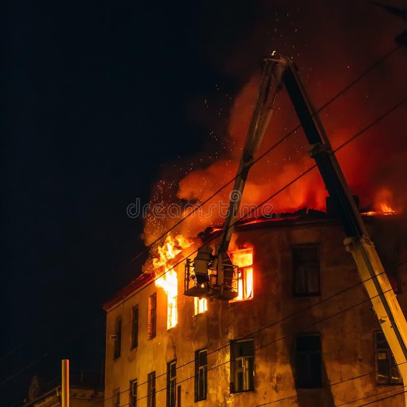 Brandmän på kranpil slåss med brand av brinnande husbyggnad på natten, katastrofen och förstörelse royaltyfri foto