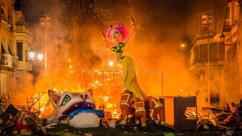 Brandmän skjuter en skulptur in i branden under Las Fallas i Valencia Spain arkivfoto