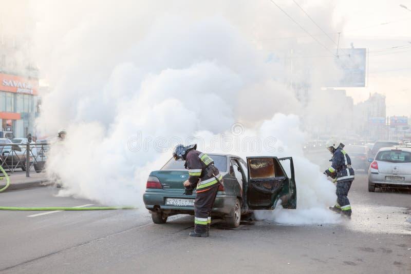 Brandmän släcker den brända bilen i stad arkivfoton