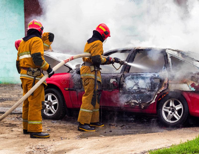 Brandmän släcker en brinnande bil, brand och bil arkivfoto