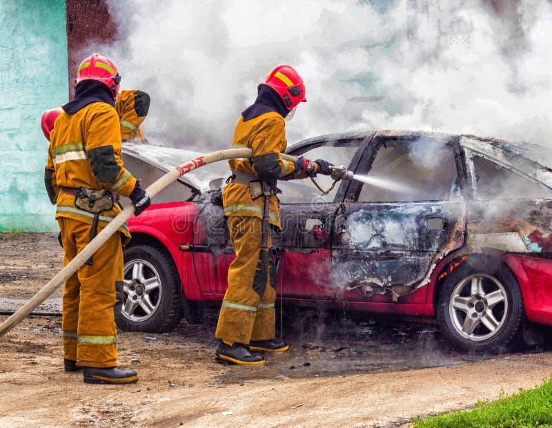 Brandmän släcker en brinnande bil, brand och bil royaltyfri fotografi