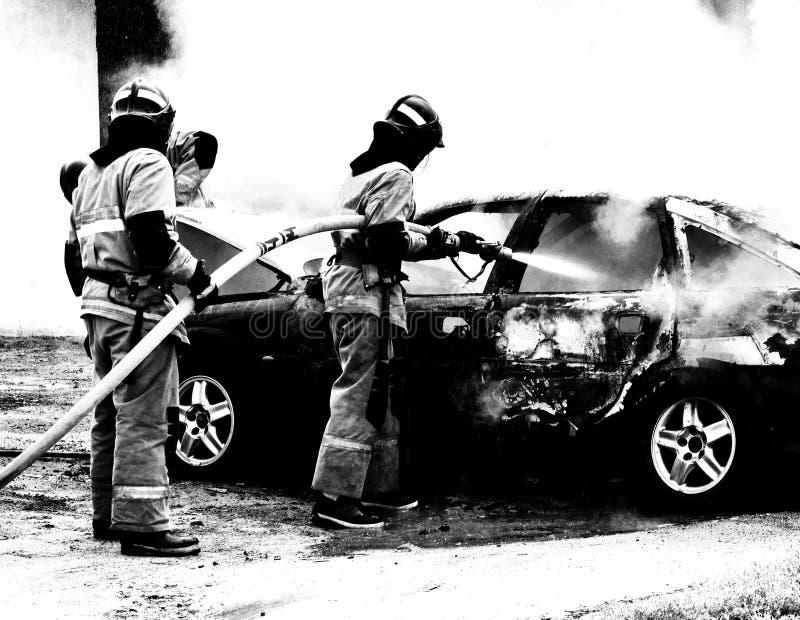 Brandmän släcker en brinnande bil, brand och bil som är svartvita arkivfoto