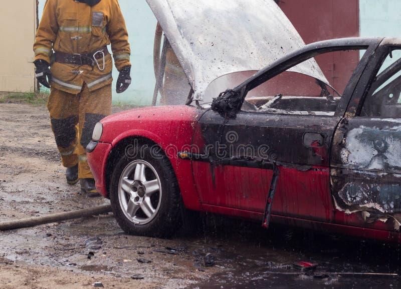 Brandmän släcker en brinnande bil med vatten, avfyrar, släcker arkivbild