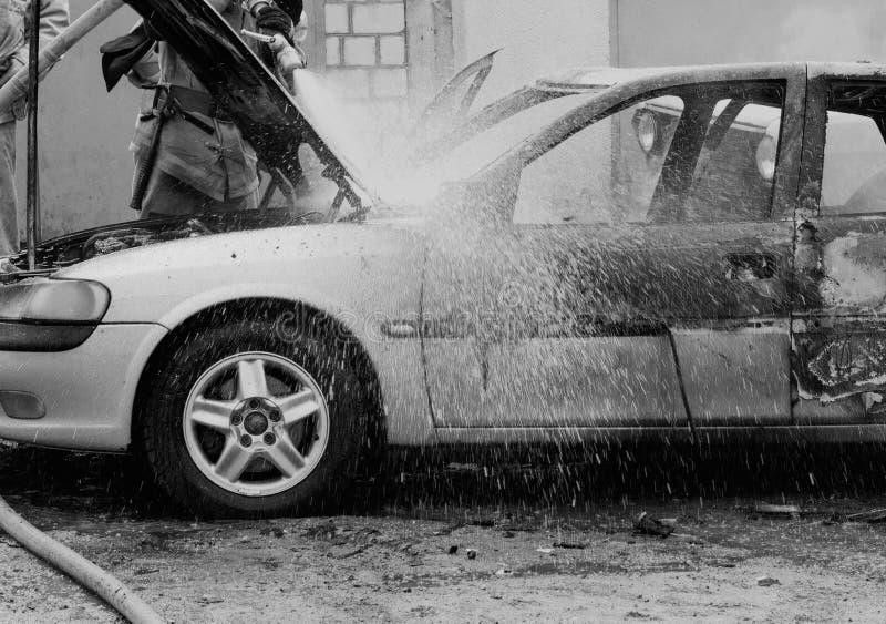 Brandmän släcker en brinnande bil med vatten, avfyrar, släcker, svartvitt royaltyfri foto