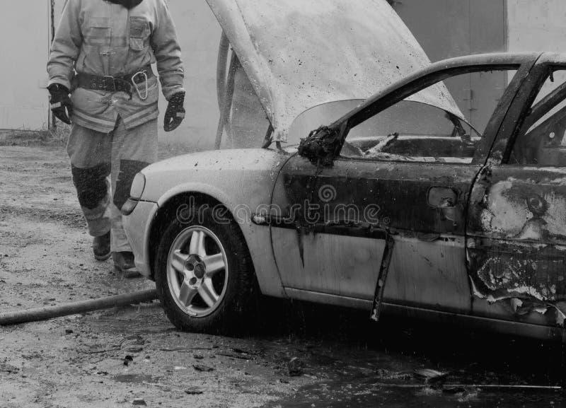 Brandmän släcker en brinnande bil med vatten, avfyrar, släcker, svartvitt royaltyfri bild