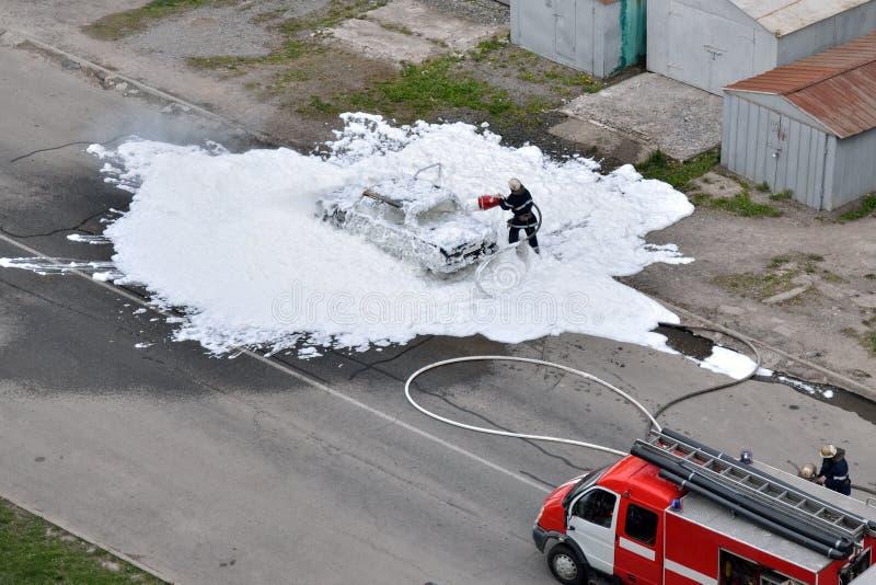 Brandmän släcks av en brinnande bil för skum royaltyfria bilder