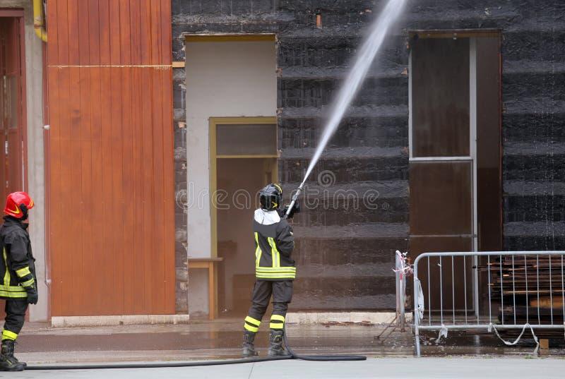 Brandmän släckte branden i byggnaden royaltyfri fotografi
