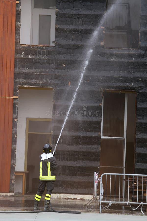 Brandmän släckte branden i byggnaden under practi royaltyfri foto