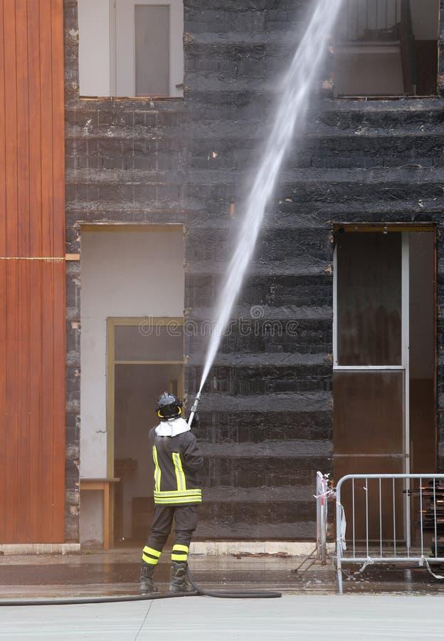 Brandmän släckte branden i byggnaden under practi royaltyfria foton