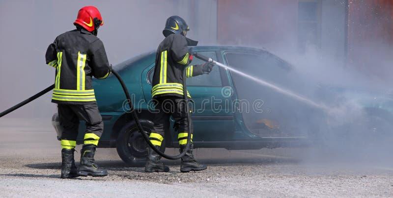 Brandmän släckte branden på en bil fotografering för bildbyråer