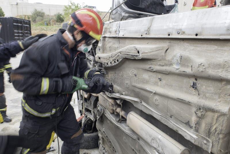 Brandmän som öva räddningsaktiontekniker i trafikolyckor royaltyfri bild