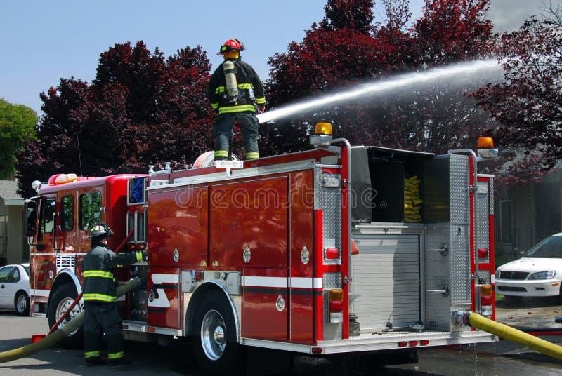 Brandmän som använder vattenkanonen på brandlastbilen för att sätta ut lägenhetbrand arkivfoton