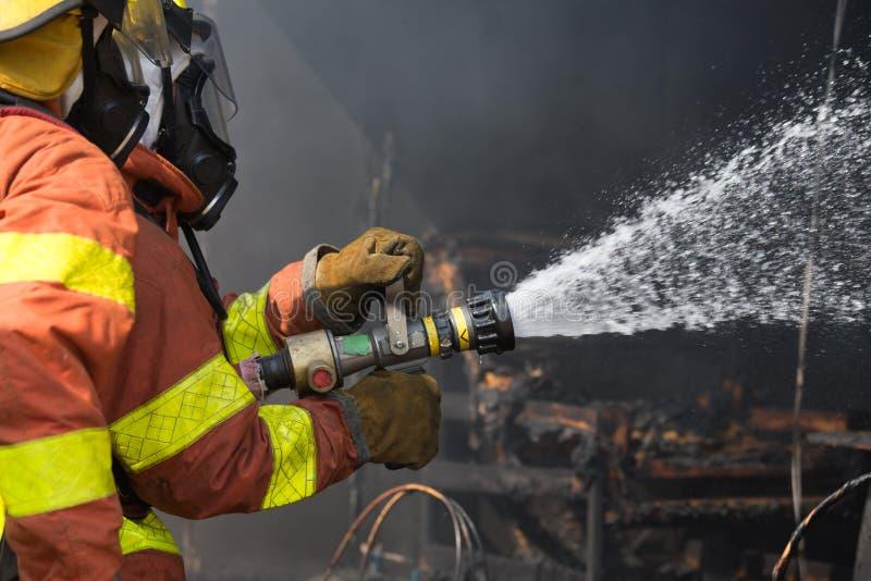 2 brandmän som besprutar vatten i operation för slåss för brand fotografering för bildbyråer