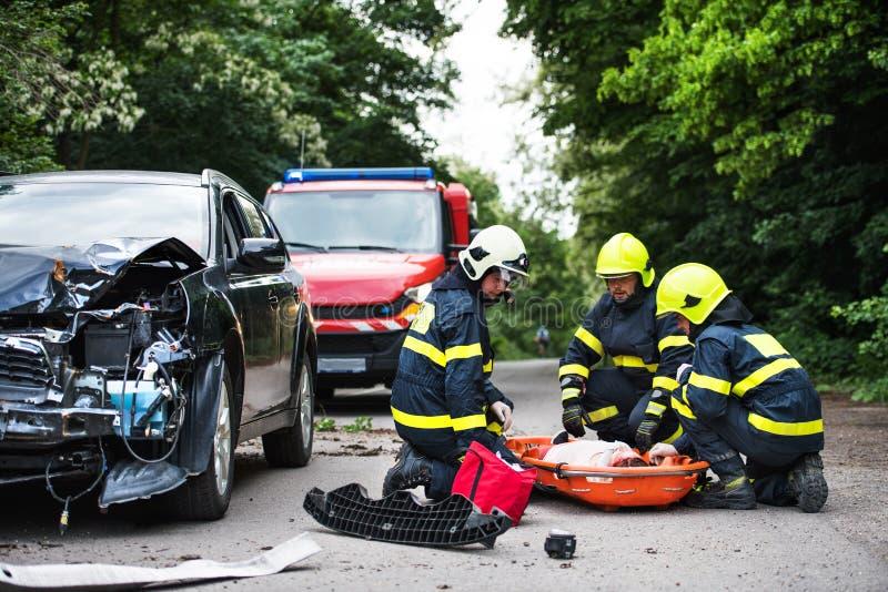 Brandmän som hjälper en ung sårad kvinna efter en bilolycka royaltyfria foton
