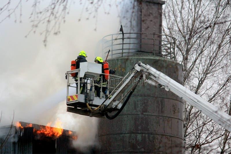 Brandmän som släcker brand på hydrauliska Crane Platform fotografering för bildbyråer