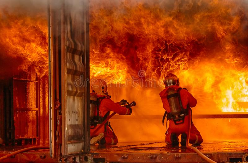 Brandmän som slåss en brand, brandmanutbildning arkivfoton