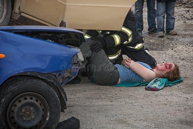 Brandmän som sparar den blödande kvinnan från en kraschad bil fotografering för bildbyråer