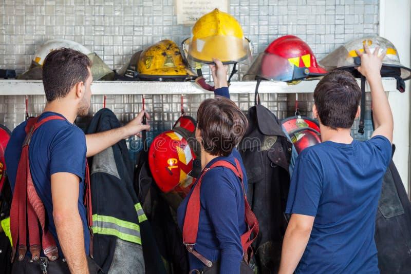 Brandmän som tar bort hjälmar från hylla royaltyfri fotografi
