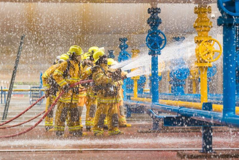 Brandmän som utbildar, förgrund är droppe av vattenspringeren fotografering för bildbyråer