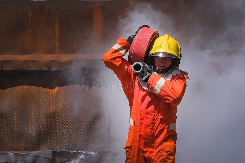 Brandmän som utbildar lagövning till att slåss med brand i nöd- läge En brandman bär en vattenslang som körs till och med flamman royaltyfria foton