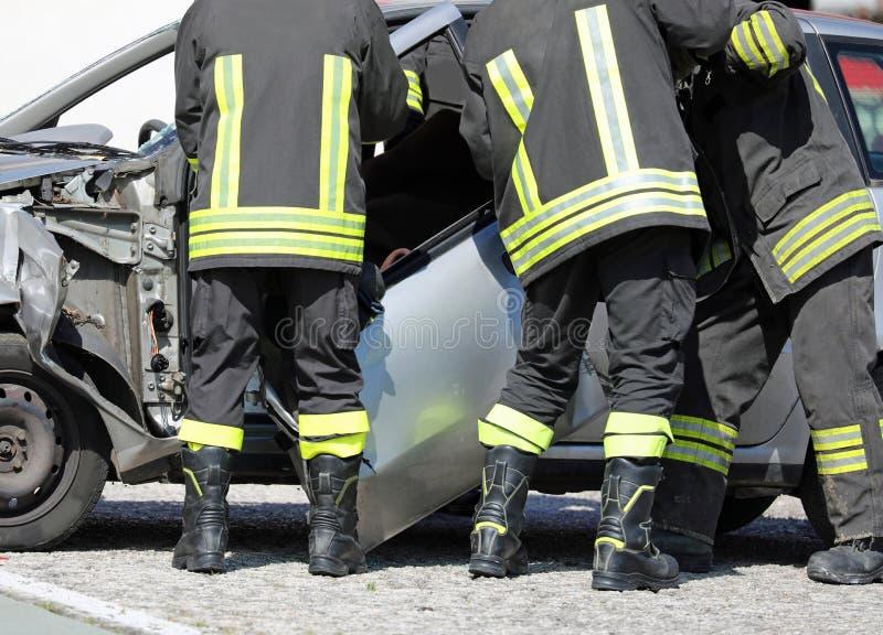 brandmän tar bort dörren av en bil efter en bilolycka för att återställa royaltyfria bilder
