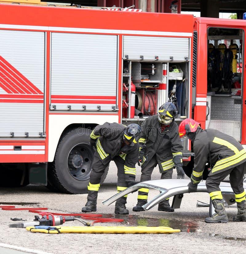 Brandmän under en vägolycka med bilen särar arkivfoto