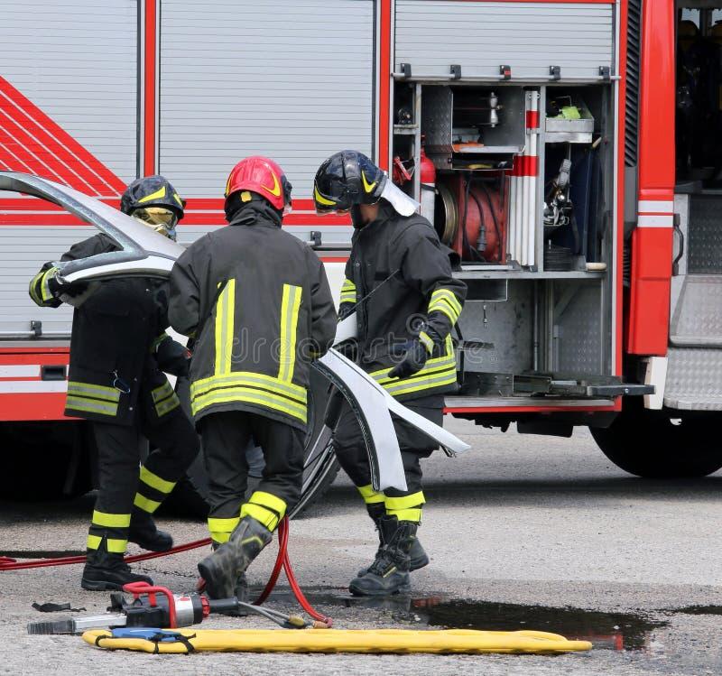 Brandmän under en vägolycka med bilen särar royaltyfria bilder