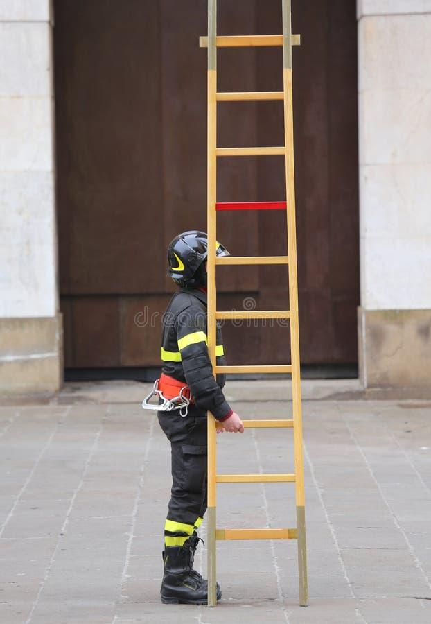 Brandmän under räddningsaktioner med en trästege royaltyfria bilder