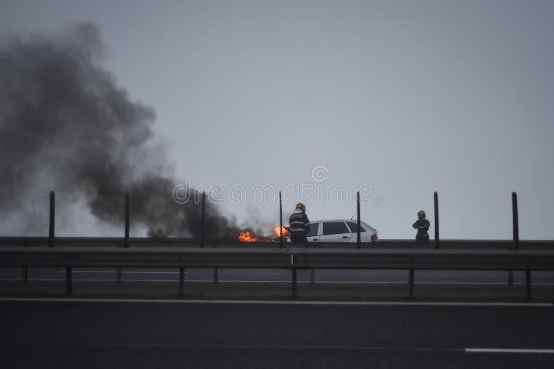 Brandm?n sl?cker en brinnande bil p? en huvudv?g royaltyfri bild