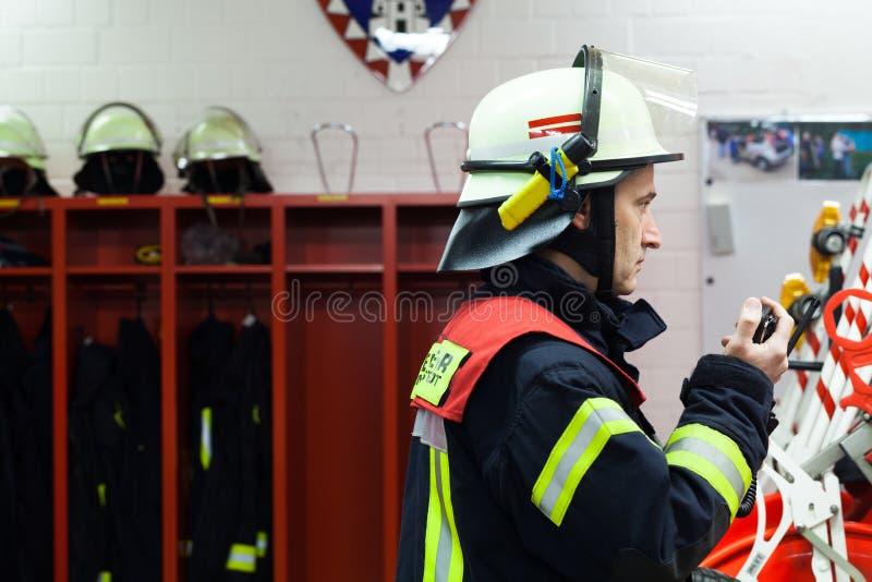 Brandman i en brandstationgnista med radiouppsättningen arkivbilder