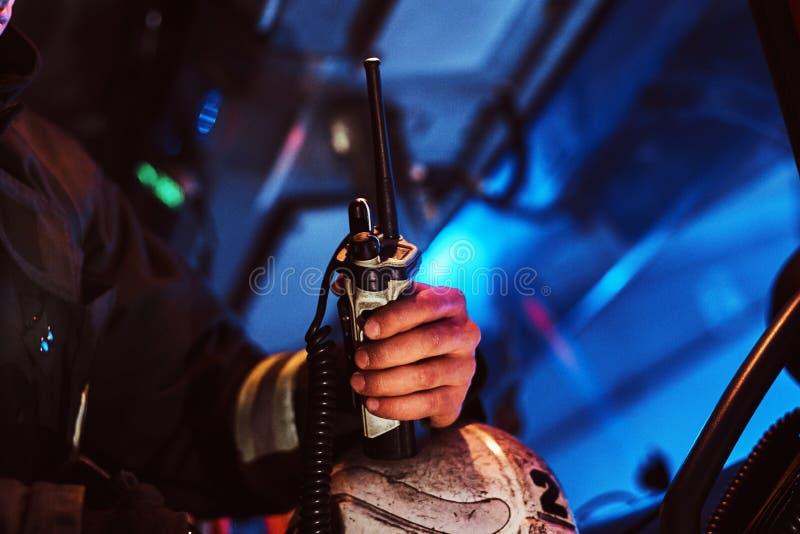 Brandman i en skyddande likformig som sitter i brandlastbilen och rymmer walkie-talkie tät hand upp royaltyfri foto