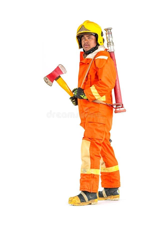 Brandman i fu för likformig och stående hållande för yxa för säkerhetshjälm arkivfoto