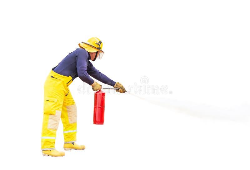 Brandman i gul likformig för brandkämpe genom att använda brandsläckaren från slangen som släcks till att slåss med brandflamman arkivbilder