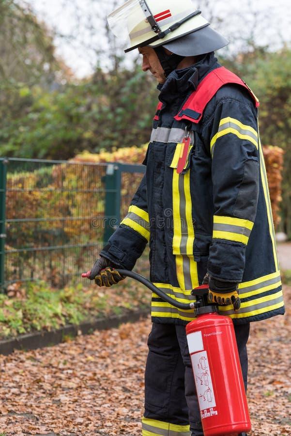 Brandman i handling med en brandsläckare royaltyfri bild