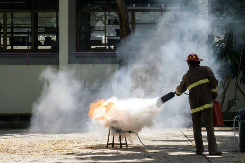 Brandman i handling med en brandsläckare fotografering för bildbyråer