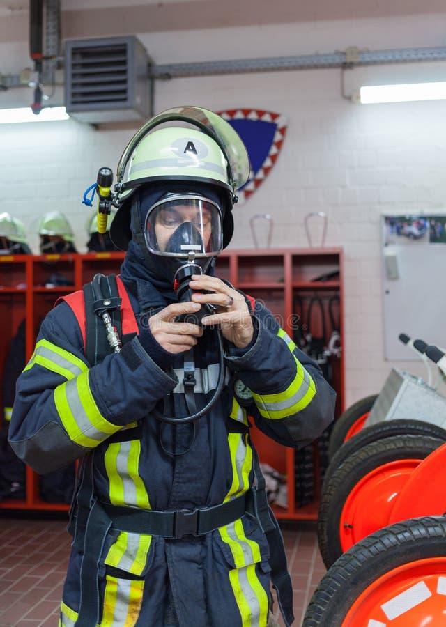 Brandman i handling och med syreflaskan och maskeringen - Serie brandman arkivfoto